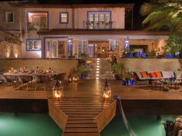 casas rurales baratas, villa en blanco y azul, patio y muelle de madrea, mesas y sofás