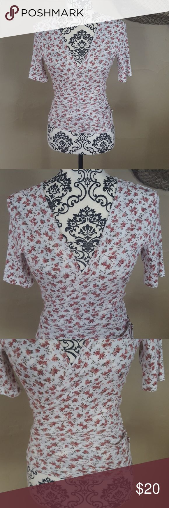 American Eagle Floral Wrap Top Brand new without tags! New style already sold out online! The top is a super light, stretchy material. Size Medium. Cream with floral print. Wraps around the front and ties in the back. Cropped but not super short. Keyhole in the back. Short sleeves. American Eagle Outfitters Tops Tees - Short Sleeve