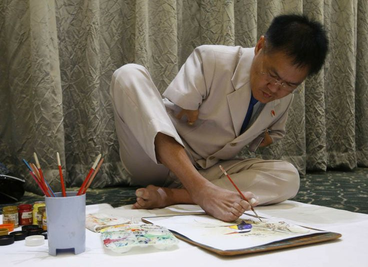 Ng Ah Kwai, 50, of Penang, Malaysia, paints with his foot during the Mouth and Foot Painting Convention in Singapore. #noveltechnique