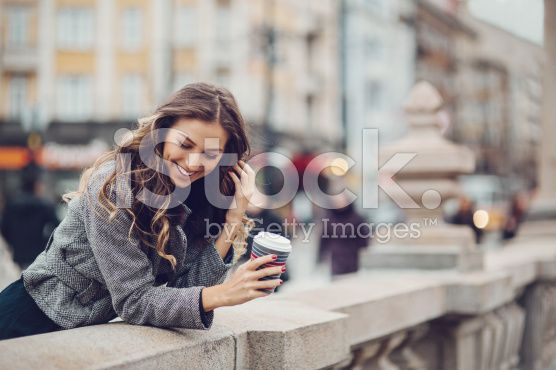Young woman with coffee cup smiling outdoors royalty-free stock photo