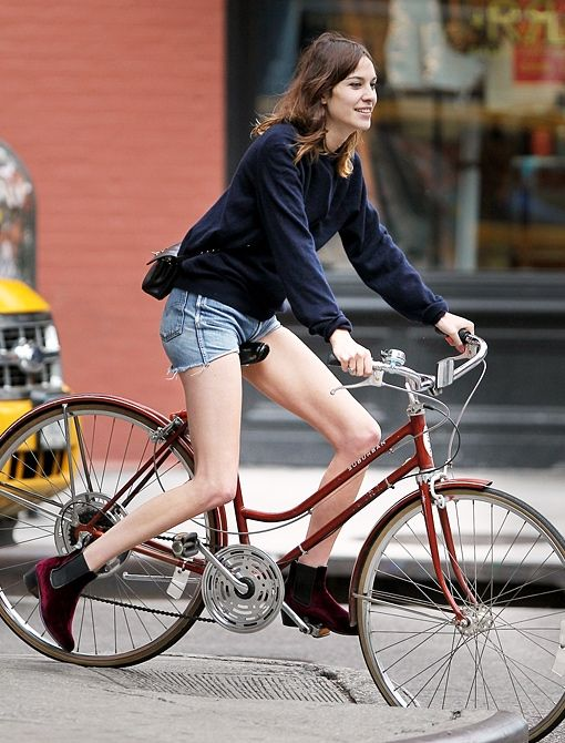 Alexa Chung on bike with denim cutoffs.