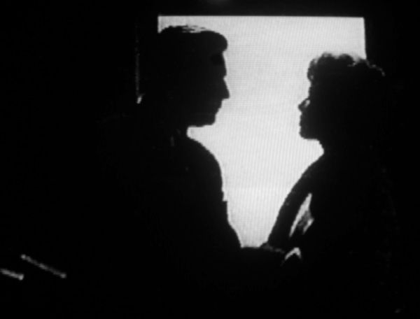 Perry and Della in the darkened front offices, their silhouettes outlined by light coming through the doorway