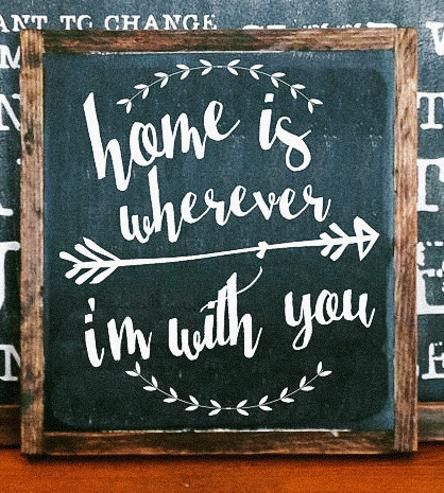 """This hand-painted wood sign celebrates who you call home, reading, """"Home is wherever I'm with you."""" The lyrics are lettered by hand and surrounded with a leafy wreath and arrow illustration in your choice of paint color. The square signage is built and framed in solid wood and distressed to add a rustic touch to any part of your home."""