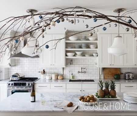 blue and white ornaments on a branch decorating a kitchen