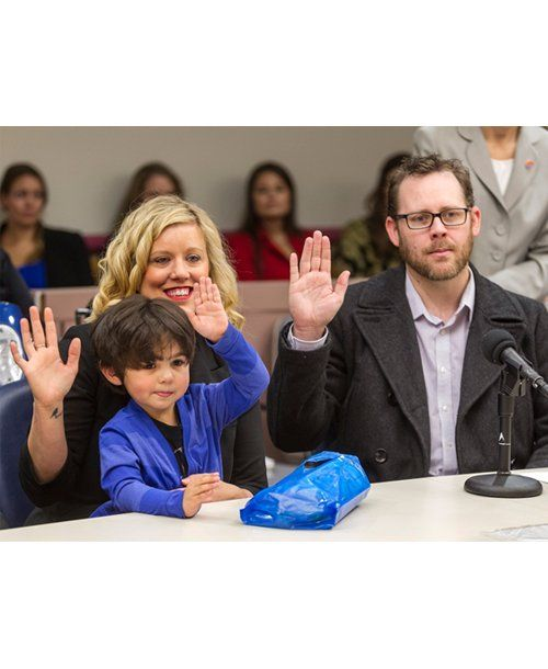 Three-year old Soul holds up his hand in court to pledge allegiance to his new adoptive parents Dennis and Katie Whitaker on National Adoption Day.