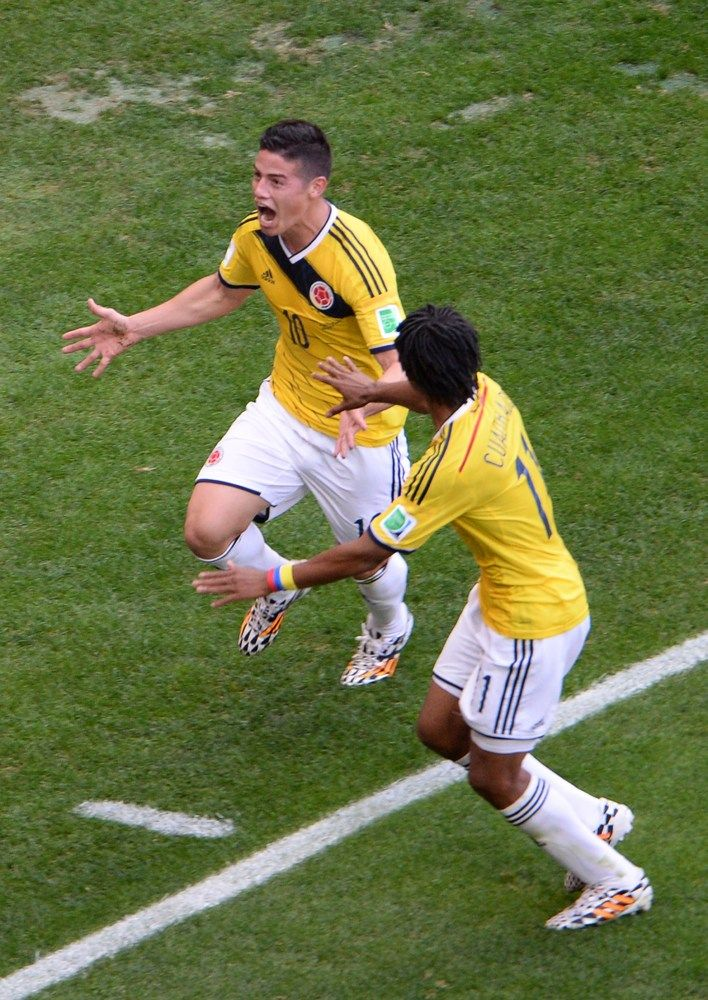Colombia Holds Off Ivory Coast 2-1 In Furious Finish At World Cup - Colombia's midfielder James Rodriguez (back) celebrates with teammate Juan Guillermo Cuadrado after scoring a goal during the Group C football match between Colombia and Ivory Coast at the Mane Garrincha National Stadium in Brasilia during the 2014 FIFA World Cup on June 19, 2014.