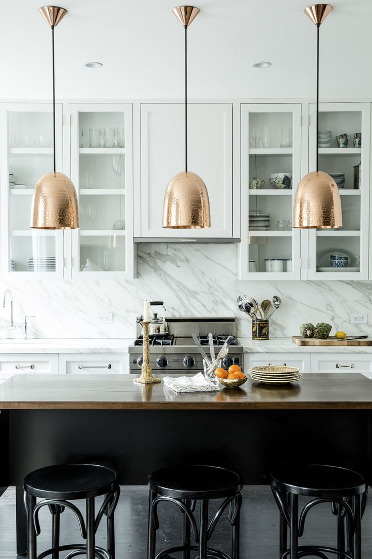 Contemporary Traditional Kitchen: A trio of hammered-copper pendant lamps above a custom wood island in a whitewashed kitchen.