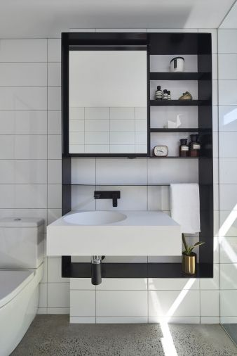 Clean, white tiles run up to the ceiling from a stone floor