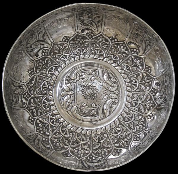 This beautiful silver hamam bowl is repoussed with a large, slightly raised central roundel decorated with foliage and floral work, surrounded by a wide border of lotus petals filled with Ottoman-style flower motifs. The exterior is decorated with a series of mihrabs with each alternate one being infilled by more Ottoman-style flower motifs.