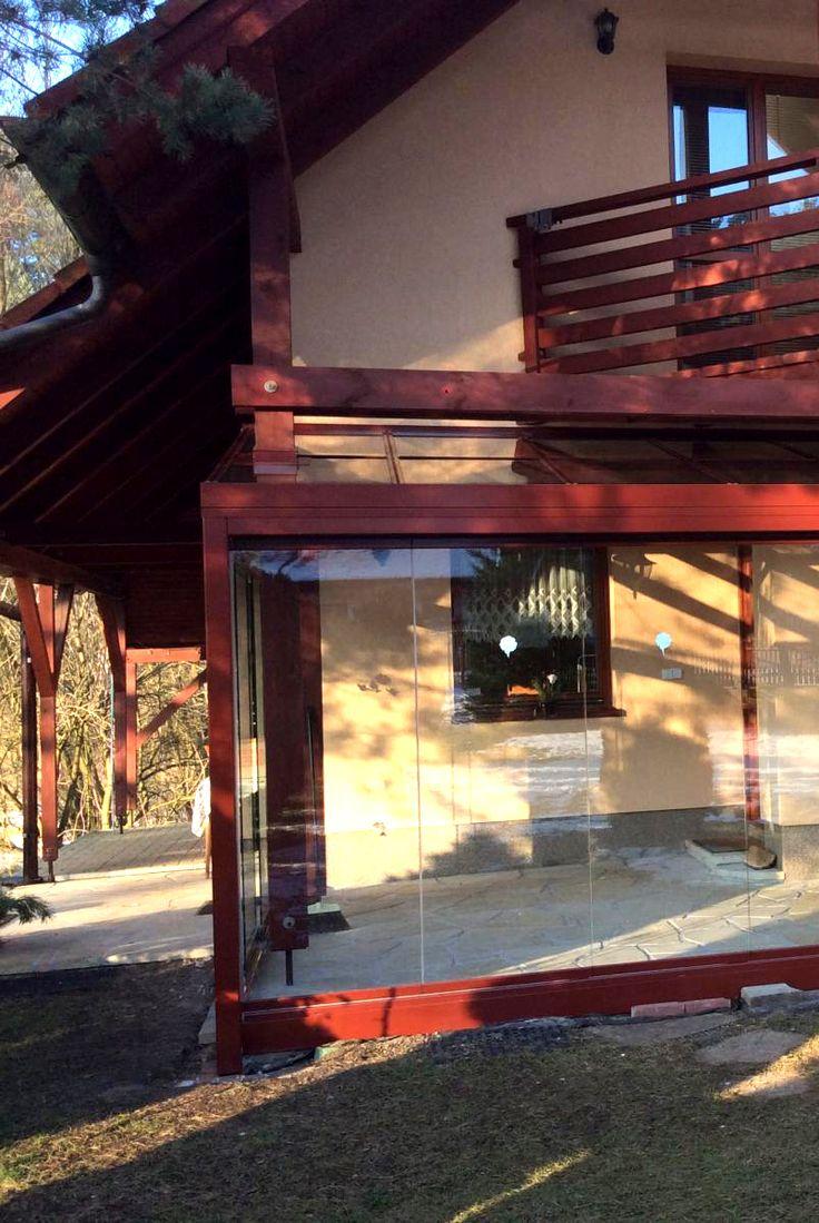 Zastřešená terasa s dřevěnými rámy a skly, které ničím neruší váš výhled do zahrady. Tradiční a zároveň moderní domov.