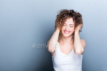 Young, smiling woman holding her curly hair up.