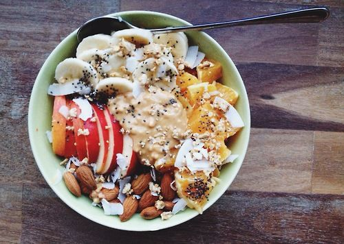 Carrot cake oatmeal topped with apple, banana, orange, almonds, peanut butter, chia seeds, coconut chips and honey.