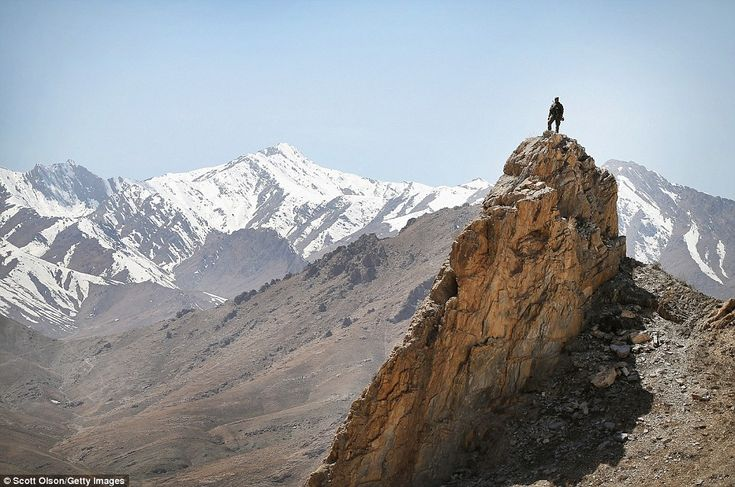 An Afghan National Army soldier looks out from a rocky overlook as American soldiers patro...