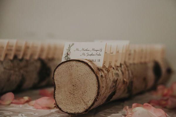 Outdoor wedding decor inspiration: woodcut escort cards created using notched logs.