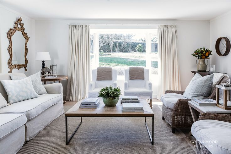 Neutral living room with sisal rug, white slip covered chairs, rattan lounge chairs, linen sofa, iron and timber coffee table. Cushions in Kravet fabric | Cottonwood Interiors. Photo by Maree Homer.