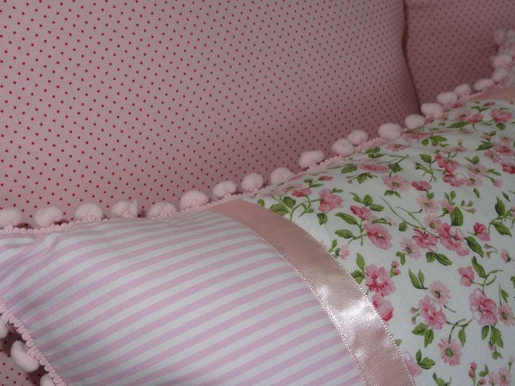 Detalhe almofada 35x45 em patchwork. Composê de 2 tecidos 100% algodão, detalhe em fita de cetim, franja em pompom e capa com acabamento em manta acrílica (matelassê).