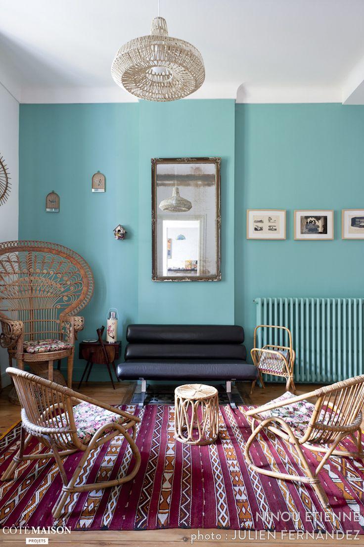 Pour ce salon, un style bohème chic mis en valeur par le mur turquoise.