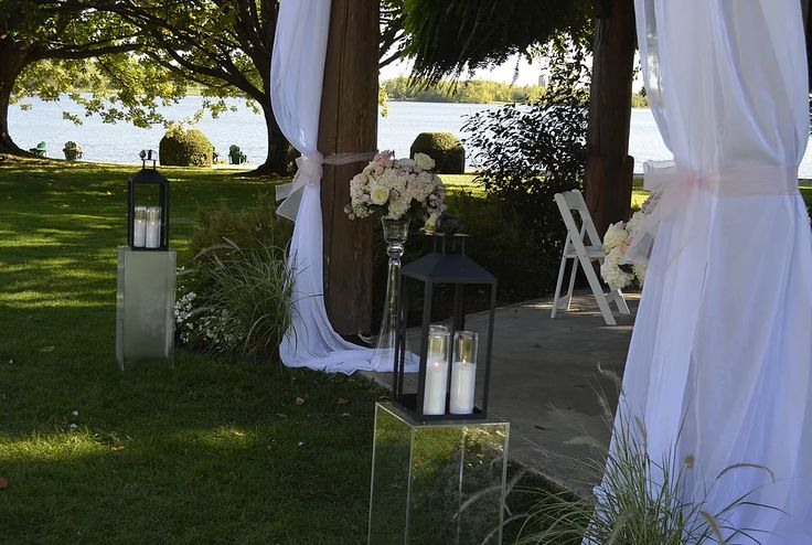 Charming outdoor ceremony at the gazebo on the grounds at Fairmont Chateau Montebello.  Lanterns, sheer drape, candles, hydrangeas, very romantic.