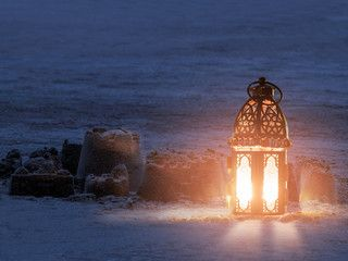 Lantern lighting with candle inside it.