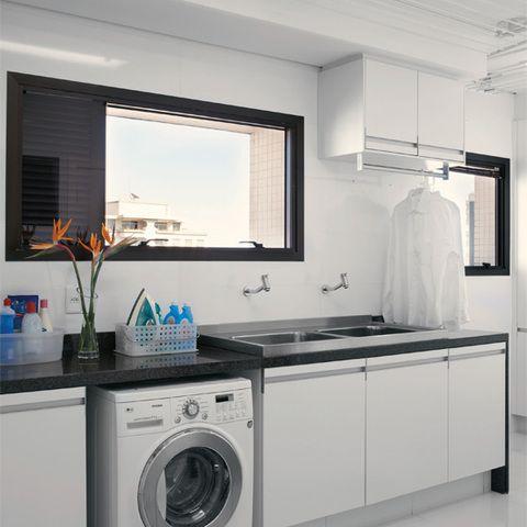 Nesta lavanderia, a lava-e-seca de 8,5 kg (LG) está na medida para um casal. A área tem varal eletrônico (Pluma Varais), armários da Ornare e piso da Portobello.
