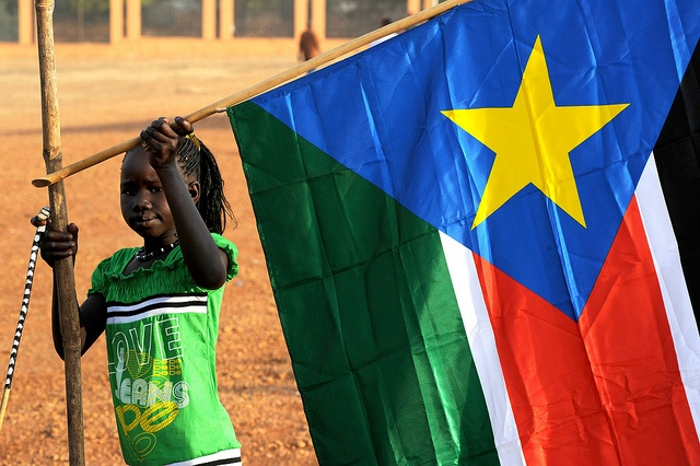 A young girl hangs the South Sudan flag (Timothy McKulka/USAID)