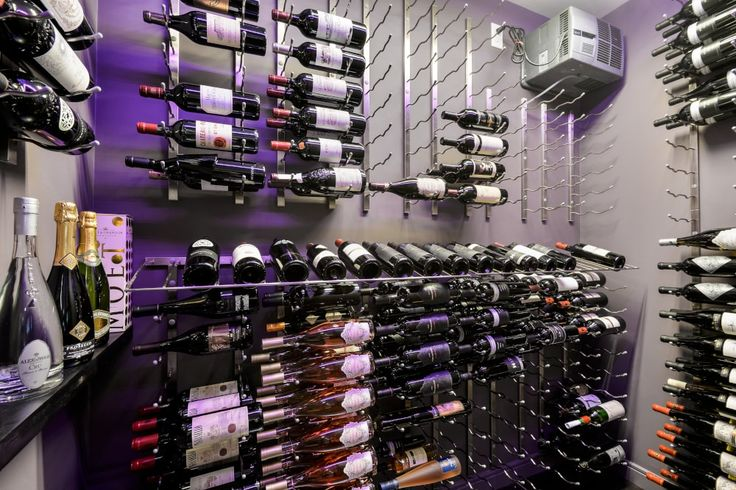 steel wine pegs label forward wine rack system in walk in wine cellar in modern bar in basement