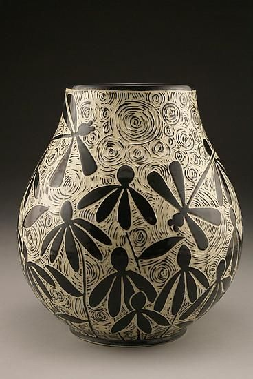 Dragonflies and Coneflowers by Jennifer Falter. Wheel thrown porcelain vase with whimsical dragonflies in a garden of coneflowers. The surface of this vase is hand carved through a layer of black slip to create a contrasting and textural surface, using a technique known as sgraffito. Each piece is unique. Size and design may vary slightly from image shown. Signed on the bottom. Dishwasher safe.
