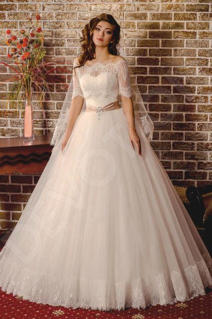 This Victorian-inspired wedding gown is the perfect fit for a modern day queen.  This unique-cut masterpiece highlights your slender figure, and the light draping on the corset adds volume in all the right places. The voluminous tulle skirt with a lace hem is both elegant and light, and the contrasting sash with a broche detail adds an exquisite finishing touch.  In a gown like this, you won't need a crown to be a queen.  * Bolero is included in the price.  ** Other accessories...