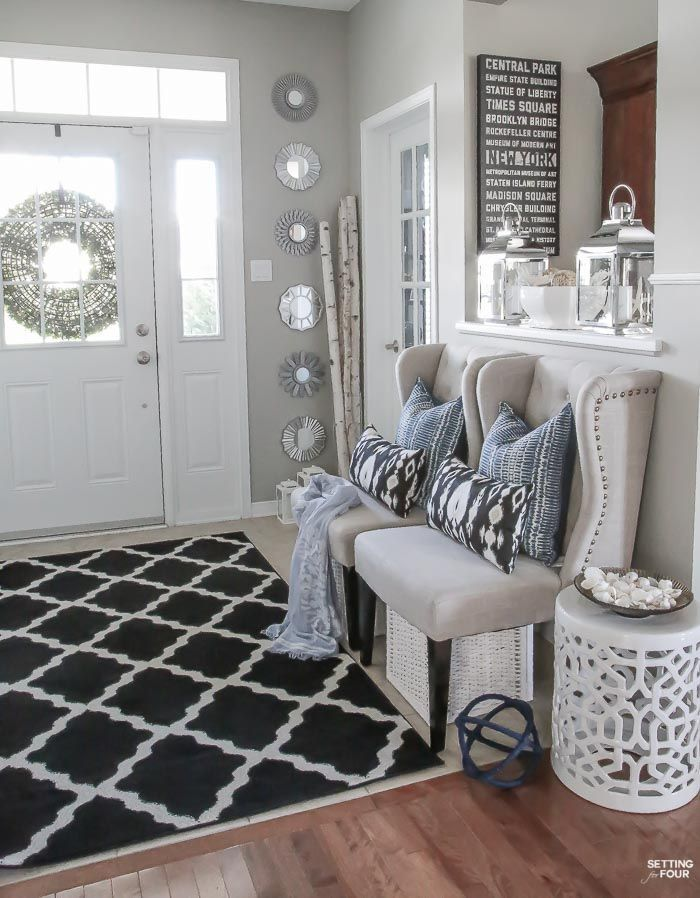 Summer home tour and summer decorating ideas. Foyer with wingback chairs, indigo shibori pillows, ikat pillows, garden stool, sunburst mirror gallery wall, birch vases, silver candle lanterns and trellis area rug