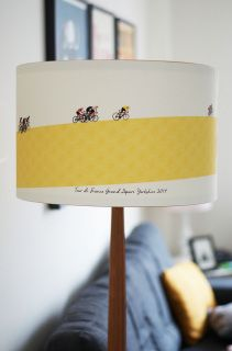 To celebrate the Tour De France departing from Yorkshire I have created a limited edition range of Lampshades They feature vintage style cyclists cycling around a graphic patterned yellow road. The background is a pale cream to keep with the vintage theme.  Printed onto a woven cotton, and backed onto flame retardant PVC. They are covered in a protective matte lacquer. Finished top and bottom with a solid wooden ring creating a look of simplicity.