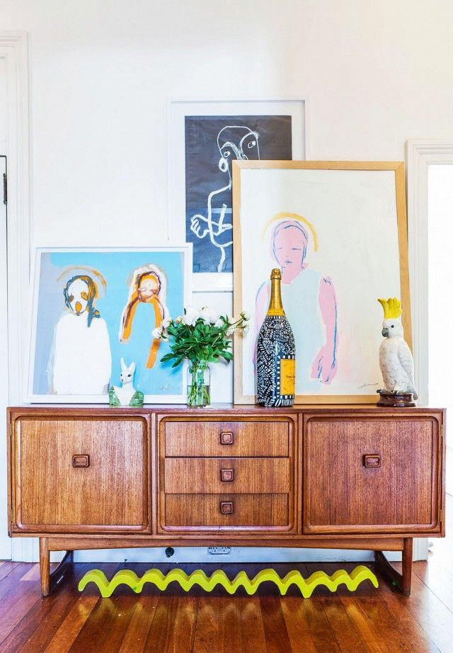 Entryway with a vintage cabinet, and art propped up on top of it.