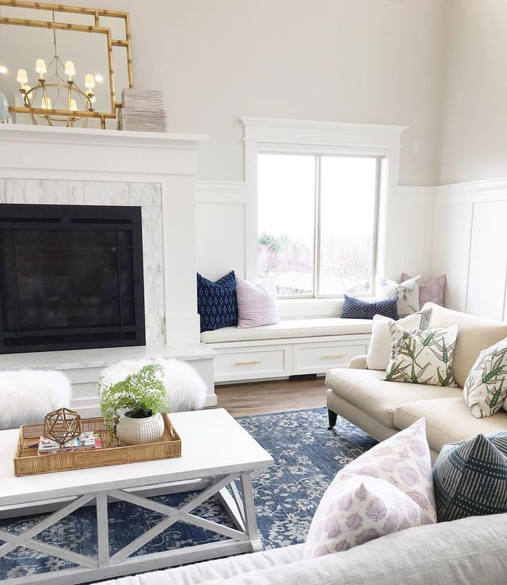 White Living Room With Fireplace Light Wood Floors And Chandelier And Window Seat