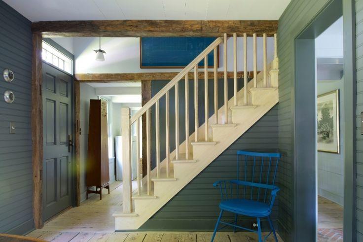 No foyer junto à escada, as paredes de madeirinha ganharam pintura cinzenta. Ali, as vigas robustas foram deixadas à mostra. Destaque ainda para a cadeira antiga, modelo Windsor, pintada de azul.  Fotografia: Jane Beiles/ The New York Times.