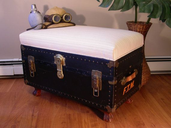 This is a real vintage trunk upcycled into a functional storage piece that would work great as a coffee table/ottoman. Carved feet bolt