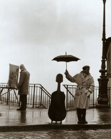 he's protecting his cello! yay. #umbrella #trenchcoat #hat