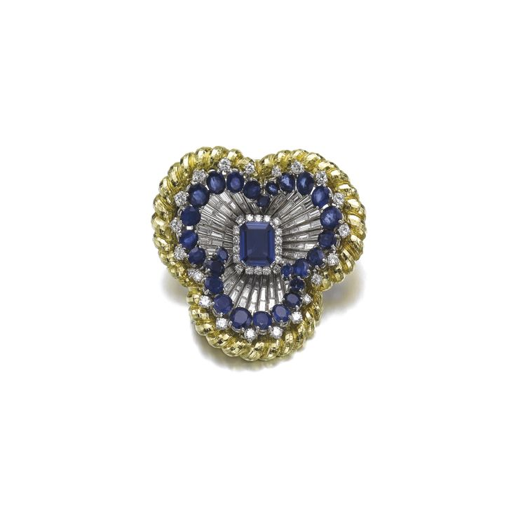 Sapphire and diamond pendant/brooch, David Webb. Designed as a pansy, set with a 6.41 carat step-cut sapphire, within a surround of brilliant-cut diamonds, the petals set with tapered baguette and brilliant-cut diamonds, oval and circular-cut sapphires.