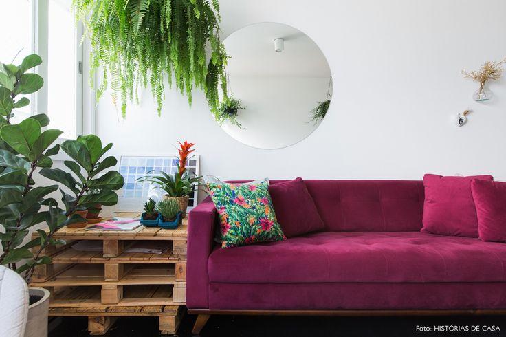 Mesa lateral feita com pallets empilhados, muitas plantas e sofá na cor beringela.