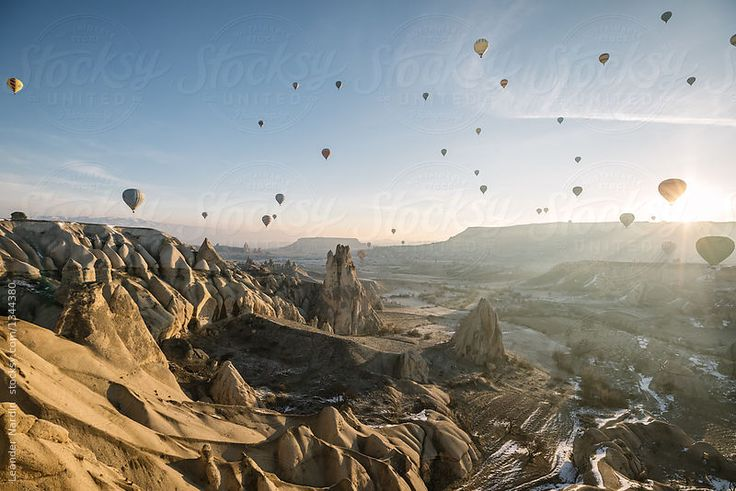 lot of colorful hot air balloons above rugged sandstone landscape of cappadocia at sunrise, turkey by Leander Nardin for Stocksy United
