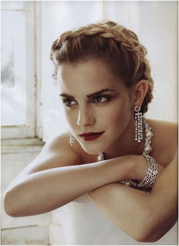 Emma Watson models Art Deco jewellery with a platted up do and signature red lips