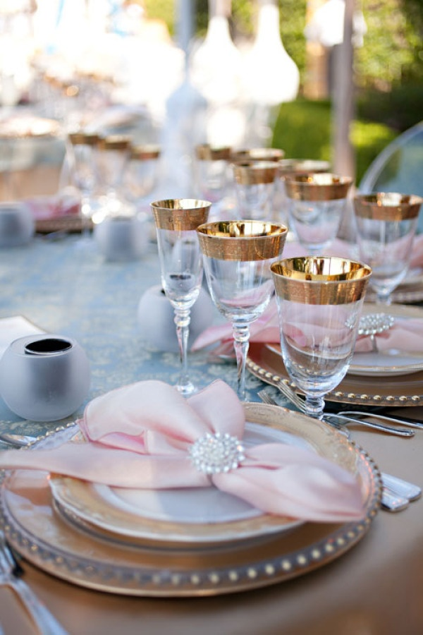 Pink bow napkins, gold china, and gold-rimmed stemware.