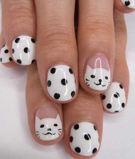 cat nails design:To get this look, make a white rounded tip for the face and add two small triangles for the ears. Now draw two black dots for the eyes and one for nose. Draw mouth and mustaches of the cat. Do polka dots on all other nails. Top coat your nails to seal in your design.