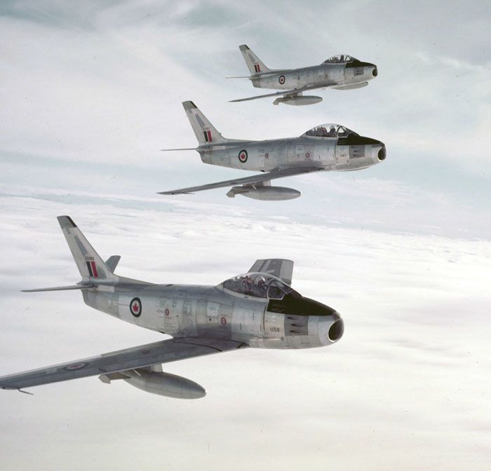 Three factory-fresh bare metal F-86 RCAF Sabres in close formation.[700672]