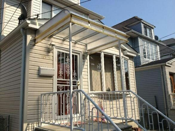 Beautiful lexan polycarbonate awning from elite awning builder awning supplier company in Queens new york. This is a clear plexiglass awning with artwork stripes gutter and posts. Attached to house outdoor awning.