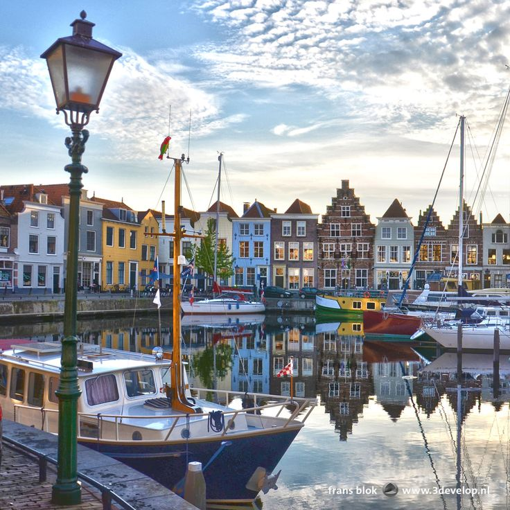 Boten en oude panden weerspielen in het rimpelloze oppervlak van de oude haven van Goes bij zonsondergang - Boats and ould houses reflect in the mirror-like water surface of the old harbour in Goes, The Netherlands.