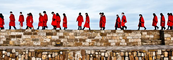 St Andrews' traditional scarlet red undergraduate robes make quite the impression at official university functions, and at the weekly Sunday pier walk.