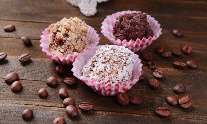 three artisan dark and white chocolates in baking cup and coffee beans on wooden table high resolution picture