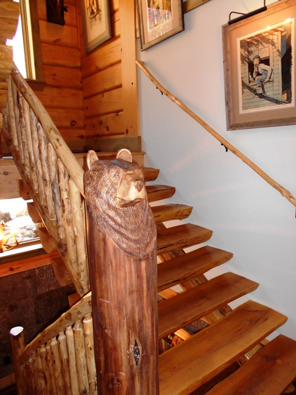 This black bear stands guard at the bottom of oak log stairs with locust log railing.