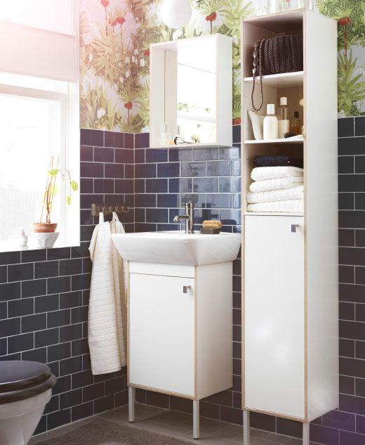 Baño con alicatado azul, un armario de lavabo blanco, un armario alto y un espejo con estante.