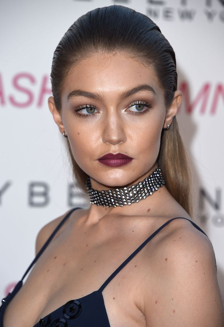 Gigi Hadid with slicked back hair, luminous white-gold lids, deep pink contoured lips and statement choker