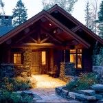 Though beautifully landscaped, the main entry is almost unassuming. Log trusses and stone pillars support the home's deep overhang and low varied roofline.